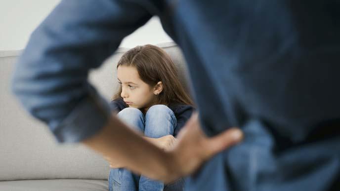 手を腰にあて立つ人物と、ふてくされてソファに体育座りの少女