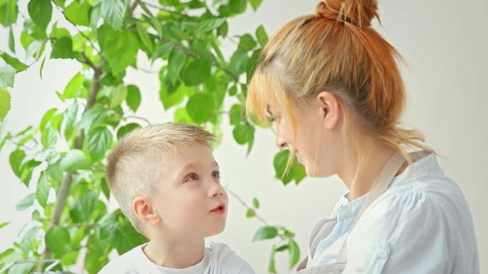 幼い息子と笑顔で向き合う若い母親