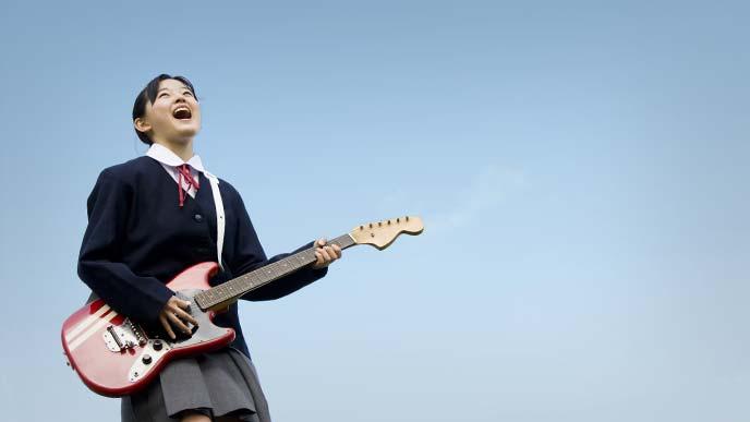 ギターを抱えて青空にジャンプする女子中学生