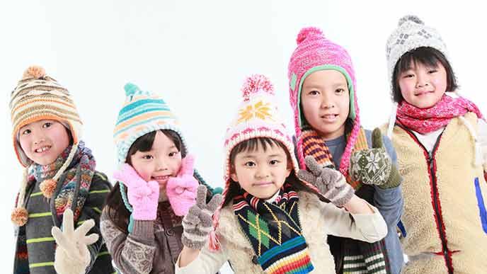 冬用のマフラーと毛糸の帽子を身に着けて並ぶ子供達