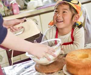 調理をしながら笑顔の子供