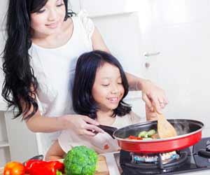 フライパンで調理する母親と子供