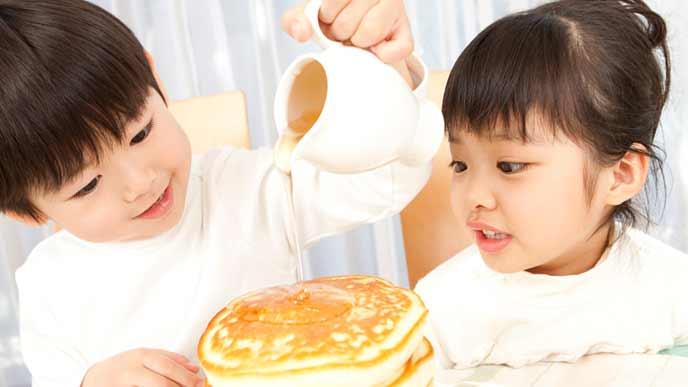 ホットケーキにシロップをかける子供