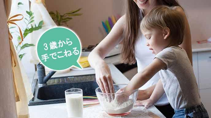 小麦粉を母親と一緒にこねる幼児