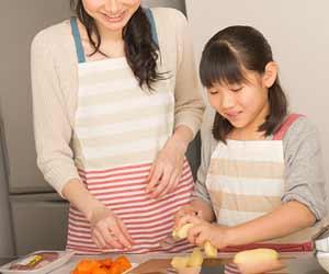 母親一緒に野菜を切る子供
