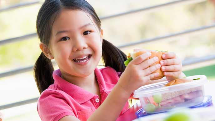 サンドイッチを手に持つ子供