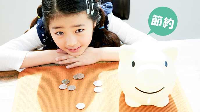 貯金箱を前に置いて貯金するお金を考える子供