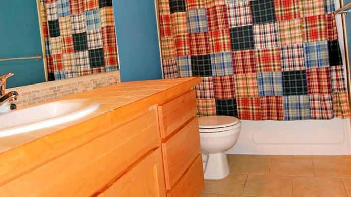 キルトを壁に掛けたトイレ