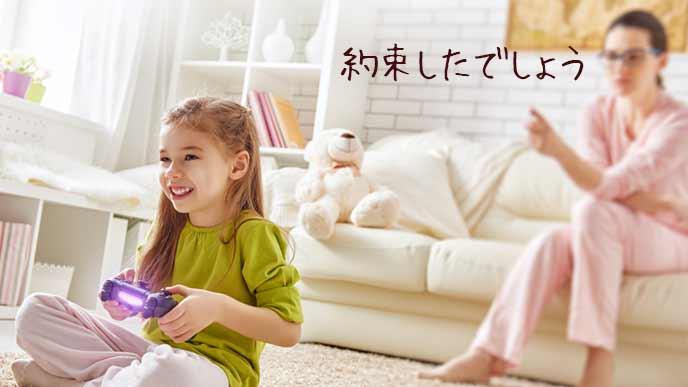 ゲームをする子供に注意する母親
