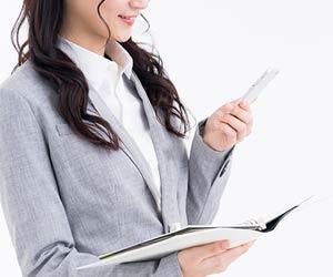 ノート見ながらスマホで電話する女性
