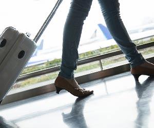 キャリーバッグを引いて歩く女性