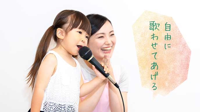 お母さんと一緒に歌を歌う幼児