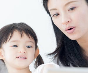 子供に歌詞を読んで聞かせる母親