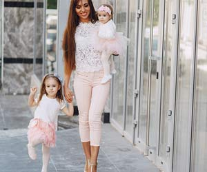 子供を抱えて歩くパンツドレスの女性