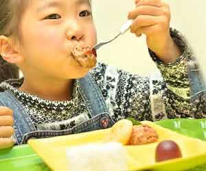 プレートに盛られたランチを食べる子供