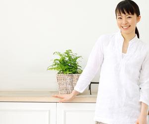 玄関の観葉植物の傍に立つ女性