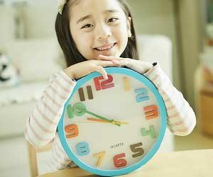 アナログ時計を抱える女の子