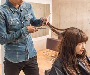 女性の髪をカットする美容師