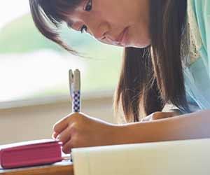 国語のドリルに書き込む小学生