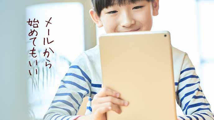 タブレットでメールを読む小学生