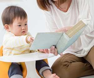赤ちゃんに図鑑を見せる母親