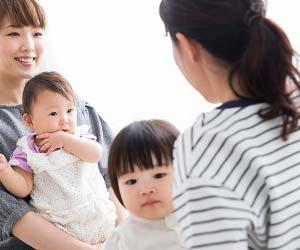 赤ちゃんを抱っこして会話する母親たち