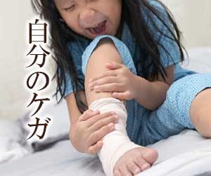 包帯を巻いた足を押さえる少女