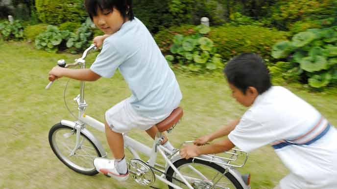 戸外で自転車遊びをする子供達