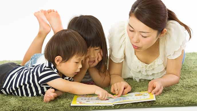 絵本を開いて指さしながら会話する親子