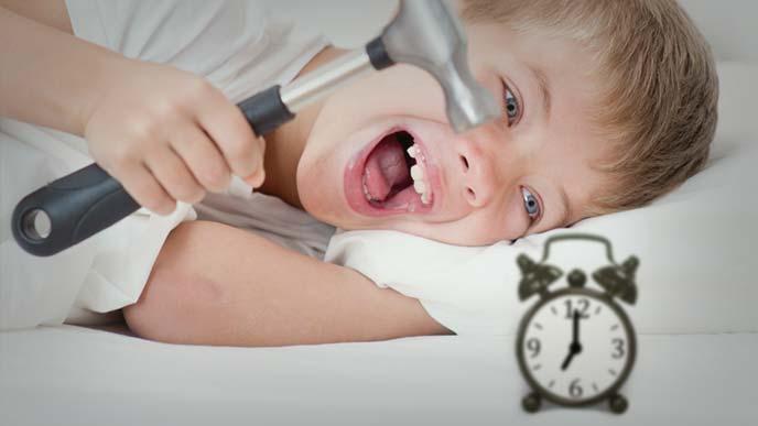 目覚まし時計を金づちで壊そうとしている寝起きの悪い男の子