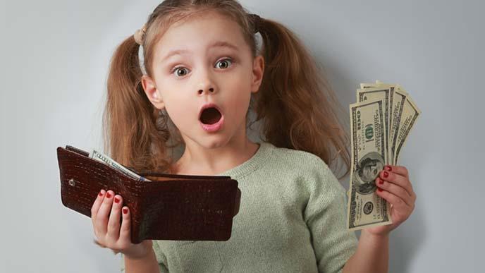 ちょっと驚きながら財布から札を取り出す女の子