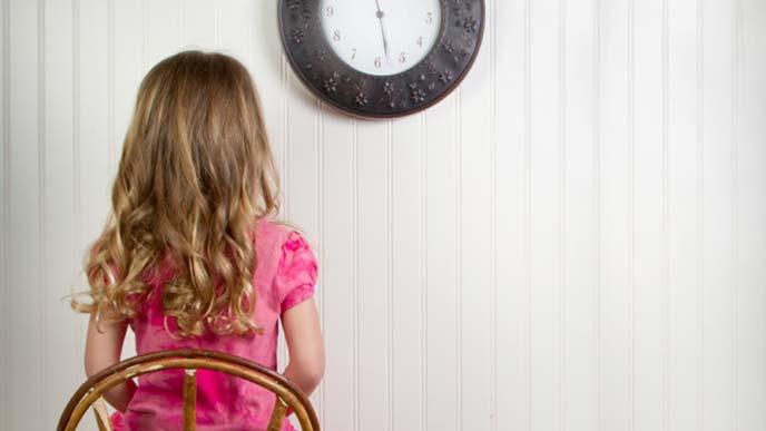 椅子に座ってじっと待機するドレッシーな女の子の背中