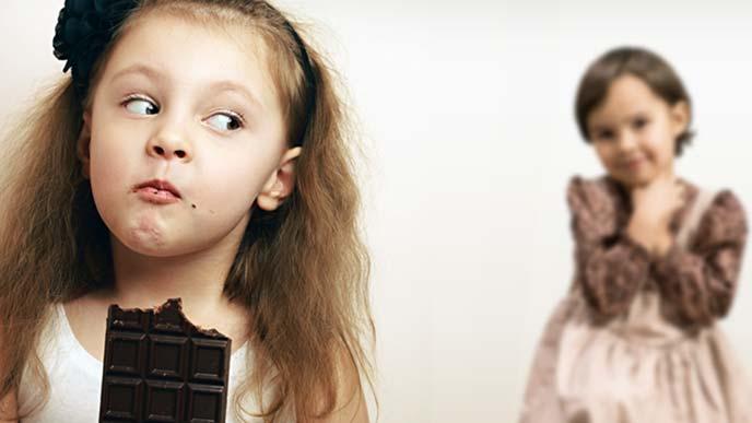 別の子の撮影を横目で見ながらチョコレートを食べる女の子