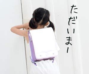 帰宅して玄関のドアをあけようとする小学生