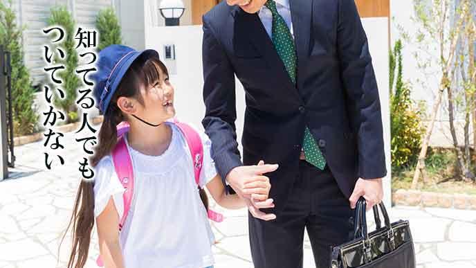 背広を着た男性に手を繋がれて笑顔の小学生