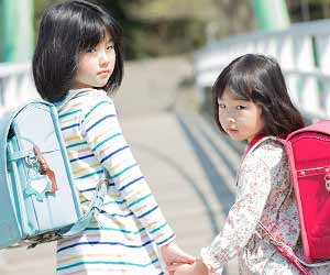 通学路で手を繋いて歩く小学生