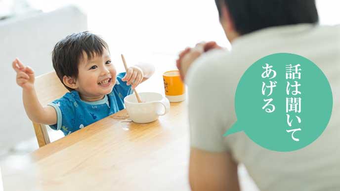 朝食時に食卓でパパに話しかける幼児