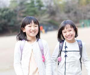 友達と二人並んで下校する小学生