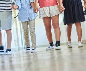 小学生が廊下に並んで立っている