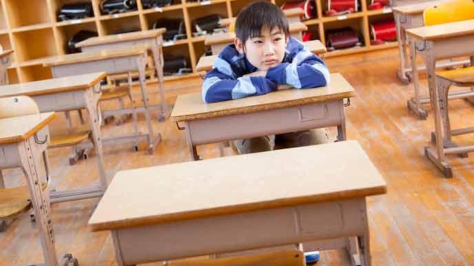 教室で一人座る小学生