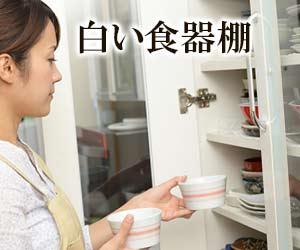 食器棚に白い器をしまう主婦