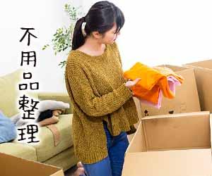 段ボール箱に囲まれて不用品を整理する女性