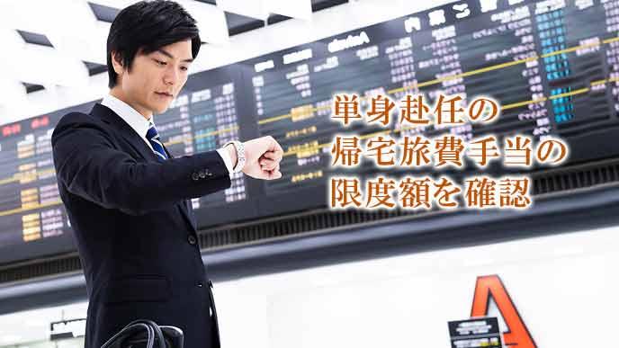 空港ロビーで時刻を確認するビジネスマン