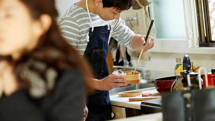 朝、お弁当を作る主夫と出かける支度をする妻