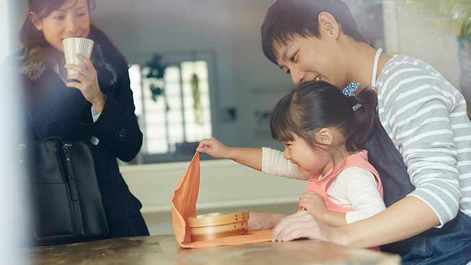 子供の弁当を準備擦る主夫と見守る妻