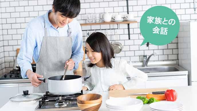 料理を作りながら子供と会話する主夫