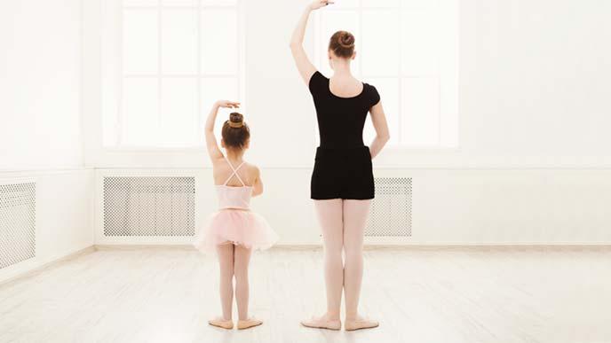 バレエを習う小さな女の子と教える女性の後ろ姿