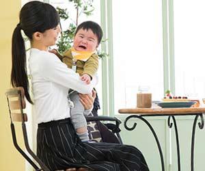 レストランで泣く赤ちゃんを抱っこする女性