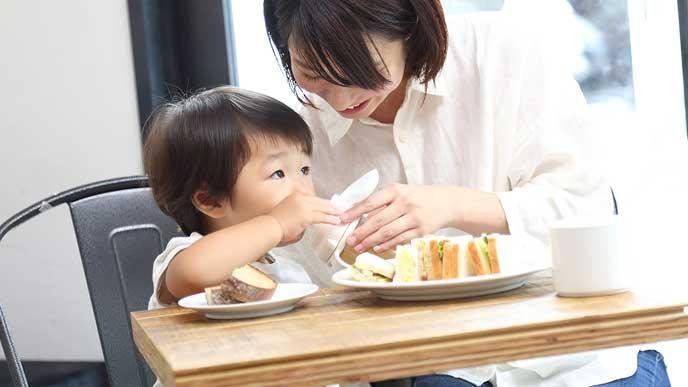 レストランで持参したマグカップで飲み物を飲む幼児