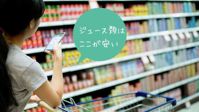 スーパーのジュース類が並ぶ棚を調べる女性